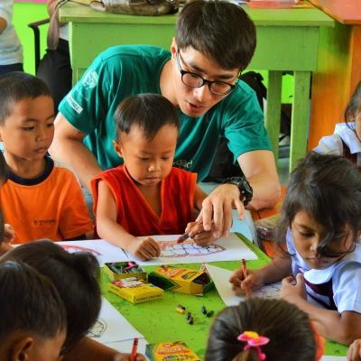 A Projects Abroad volunteer working with children in the Philippines sits with a group of kindergarten children in a classroom during his Childcare Project.